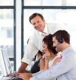 Rijpe manager in een call centre dat bij de nok glimlacht Stock Foto