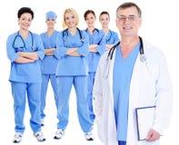 Rijpe mannelijke arts met zijn collega's Stock Afbeelding