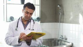 Rijpe mannelijke dierenarts die medische documenten vullen die aan de camera glimlachen stock videobeelden