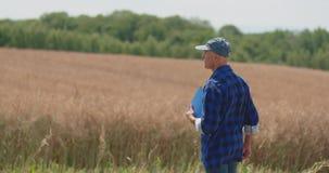 Rijpe Mannelijke Landbouwer Writing On Clipboard bij Landbouwbedrijf Moderne landbouw stock footage