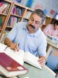 Rijpe mannelijke student die in bibliotheek bestudeert stock foto