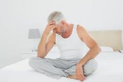 Rijpe mens die aan hoofdpijn in bed lijden royalty-vrije stock fotografie