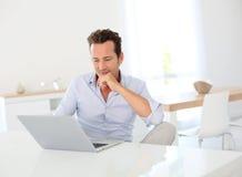 Rijpe mens die aan laptop werken stock fotografie