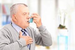 Rijpe mens die astma behandelen met inhaleertoestel Stock Fotografie