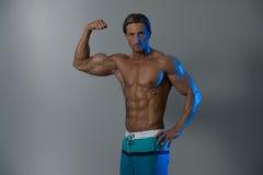 Rijpe Mens die Bicepsen op Grey Background uitwerken Stock Foto's