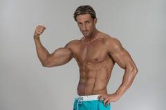 Rijpe Mens die Bicepsen op Grey Background uitwerken Royalty-vrije Stock Afbeelding