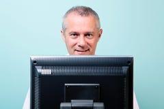 Rijpe mens die bij een computer werkt Stock Foto