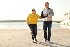 Rijpe mens die blinde persoon met lang riet helpen royalty-vrije stock fotografie