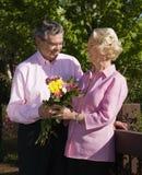 Rijpe mens die bloemen voorstelt. royalty-vrije stock foto's