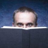 Rijpe mens die door boek worden geconcentreerd en wordt vastgehaakt stock fotografie