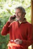 Rijpe Mens die Draadloze Telefoon thuis met behulp van Royalty-vrije Stock Afbeeldingen