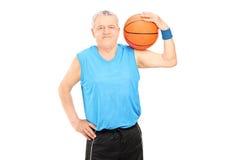 Rijpe mens die een basketbal over zijn schouder houden Stock Afbeeldingen