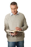 Rijpe mens die een boek leest Stock Afbeeldingen