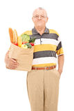Rijpe mens die een zakhoogtepunt van kruidenierswinkels houden Royalty-vrije Stock Foto's