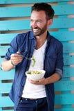Rijpe mens die gezond voedsel en het glimlachen eten stock foto's