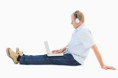Rijpe mens die laptop met behulp van die aan muziek luistert Stock Foto's