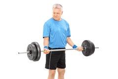 Rijpe mens die met een zware barbell uitoefenen Stock Fotografie