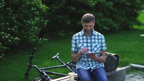 Rijpe mens die op digitale tablet doorbladeren, die op de bank in een park zitten stock video