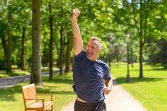 Rijpe mens die in park met het winnen van gebaar lopen stock foto's