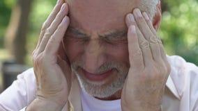 Rijpe mens die plotselinge scherpe pijn in hoofd voelen, migraineaanval, risico van bloedprop stock videobeelden