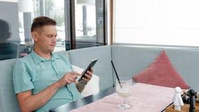 Rijpe mens die touchscreen van de tabletcomputer in koffie gebruiken stock video
