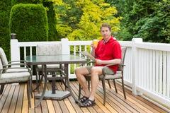 Rijpe mens die van een vers glas sap genieten terwijl buitenkant op pati Stock Foto's