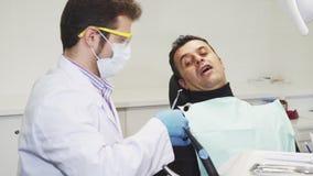 Rijpe mens die zijn tandarts bezoeken bij de kliniek stock video