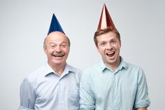 Rijpe mens en zijn jonge zoon die gelukkige verjaardag vieren die grappige kappen dragen stock afbeeldingen