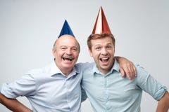 Rijpe mens en zijn jonge zoon die gelukkige verjaardag vieren die grappige kappen dragen stock afbeelding