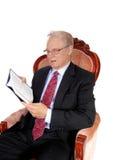 Rijpe mens in het boek van de kostuumlezing Stock Foto