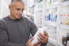 Rijpe mens het kopen medicijnen bij de drogisterij stock fotografie