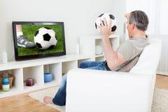 Rijpe mens het letten op voetbal op televisie Royalty-vrije Stock Foto's