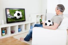 Rijpe mens het letten op voetbal op televisie stock foto