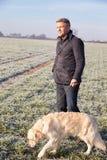 Rijpe Mens het Lopen Hond in Frosty Landscape Royalty-vrije Stock Afbeelding