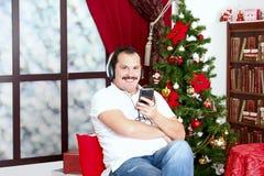 Rijpe mens het luisteren muziek op hoofdtelefoons dichtbij een Nieuwjaar tre Royalty-vrije Stock Foto's