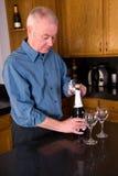 Rijpe mens het openen wijn. Stock Afbeelding
