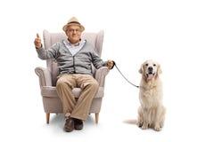 Rijpe mens met een labrador retriever-hondzitting in een leunstoel stock fotografie