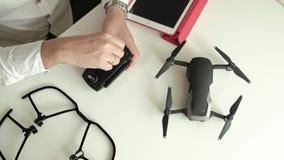 Rijpe mens met glazen en een wit overhemd die een controlebord voor een quadrocopter assembleren, concept het leren technieken stock footage