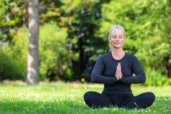 Rijpe Midden Oude Geschikte Gezonde Vrouw het Praktizeren Yoga buiten stock afbeelding