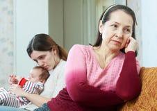 Rijpe moeder en dochter met baby na ruzie Stock Afbeeldingen
