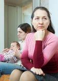 Rijpe moeder tegen dochter met baby na ruzie Stock Fotografie