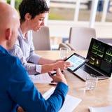 Rijpe onderneemster bezig het tonen van haar partneranalyse van elektronische tablet stock fotografie