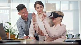 Rijpe onderneemster die 3d virtuele werkelijkheidsbeschermende brillen gebruiken op het werk stock footage