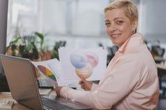 Rijpe onderneemster die op het kantoor werken stock afbeeldingen