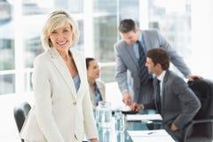 Rijpe onderneemster met collega's die in bureau bespreken Stock Afbeelding