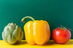 Rijpe organische het capsicumtomaat van de groentenartisjok op duotone donkergroene gele achtergrond Gezond installatie gebaseerd royalty-vrije stock foto