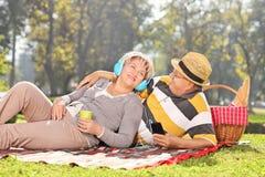 Rijpe paar het luisteren muziek op een picknick in park Royalty-vrije Stock Foto's