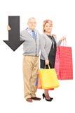 Rijpe paarholding het winkelen zakken en het grote zwarte pijl richten Stock Fotografie