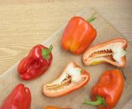 Rijpe paprika's op de bruine close-up van het keukenbureau Royalty-vrije Stock Foto's