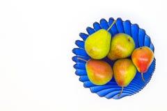 Rijpe peren in een blauwe glasvaas op een witte achtergrond Royalty-vrije Stock Afbeeldingen